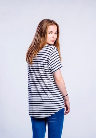 mujeres de espalda: Adolescente en pantalones vaqueros y camiseta de rayas, mujer joven, tiro del estudio sobre fondo gris, vista trasera