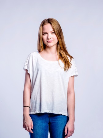 jeans apretados: Teenage girl in jeans and white t-shirt, young woman, studio shot on gray background