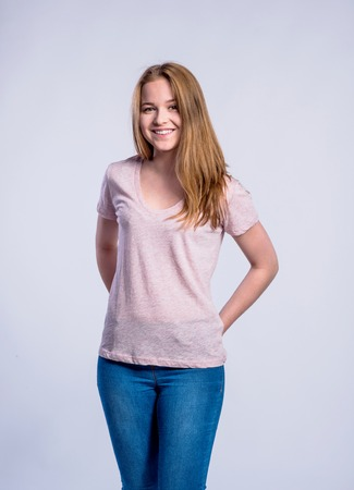 teenage girl: Teenage girl in jeans and pink t-shirt, young woman, studio shot on gray background Stock Photo