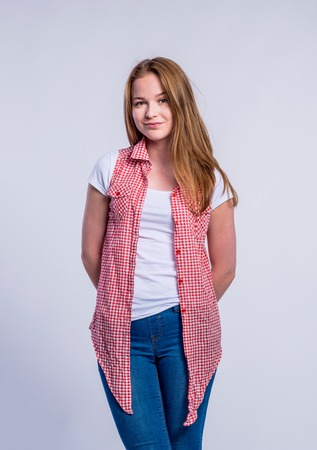 hands behind back: Teenage girl in jeans, white t-shirt and red checked shirt young woman, studio shot on gray background Stock Photo