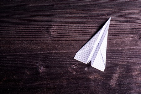 paper airplane: Old dark wooden board background, plank with texture, paper airplane, empty copy space Stock Photo