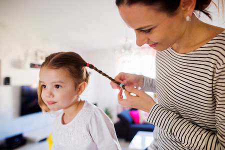 braiding: Beautiful young mother braiding hair of her little daughter in the morning
