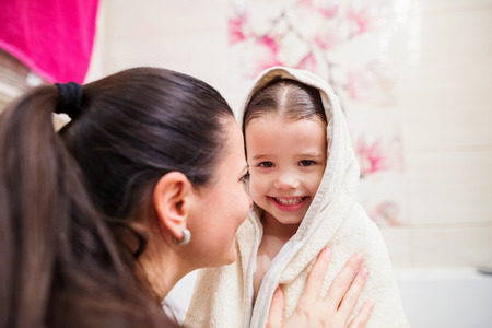Beautiful young mother drying her little daughter wrapped in towel after taking bath