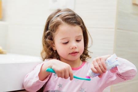 pasta dental: Niña linda en sus pijamas en el baño poniendo una pasta de dientes en el cepillo de dientes Foto de archivo
