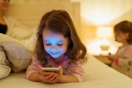 Menina bonito com smartphone deitado em uma cama, antes de dormir Imagens