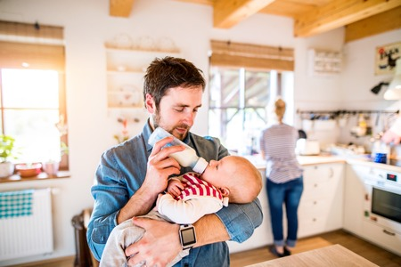 Young father feeding his cute newborn baby son, holding him in his arms Stock Photo - 56620765