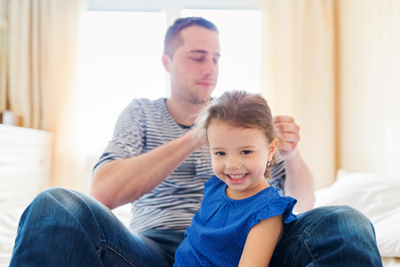 combing: Young father combing hair of his little daughter in the morning Stock Photo