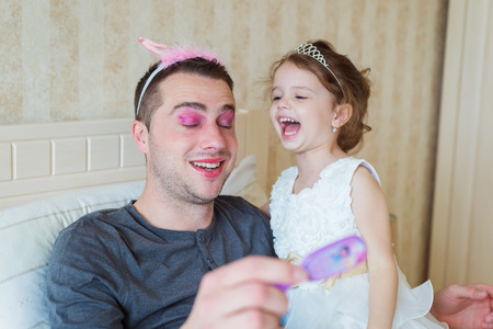 putt: Cute little girl in princess dress that putt on colorful make up on her father Stock Photo