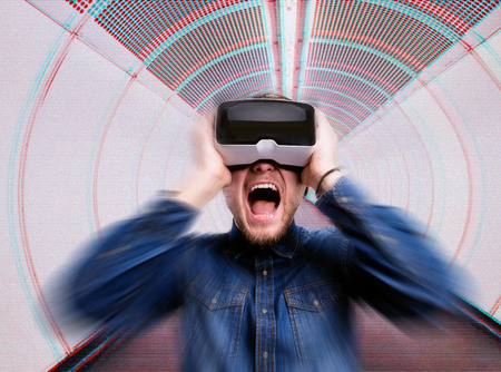 Hipster man in denim shirt wearing virtual reality goggles. Standing in corridor