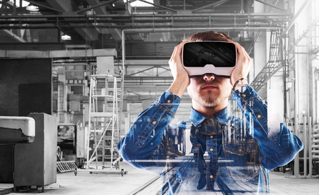 Hipster man in denim shirt wearing virtual reality goggles. Welding factory. Banque d'images