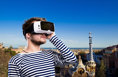 Hipster man in striped black and white sweatshirt wearing virtual reality goggles. Park Guell, Barcelona, Spain. Stock Photo