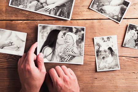 little table: Mothers day composition. Hands of unrecognizable man holding  black-and-white photo. Studio shot on wooden background.