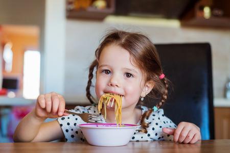 niña comiendo: Niña linda en la sonrisa de la cocina, comer espaguetis Foto de archivo