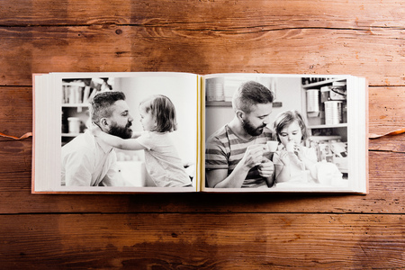 photo pictures: Fathers day composition. Photo album, black-and-white pictures. Studio shot on wooden background.