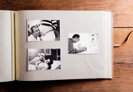 album: Fathers day composition. Photo album, black-and-white pictures. Studio shot on wooden background.