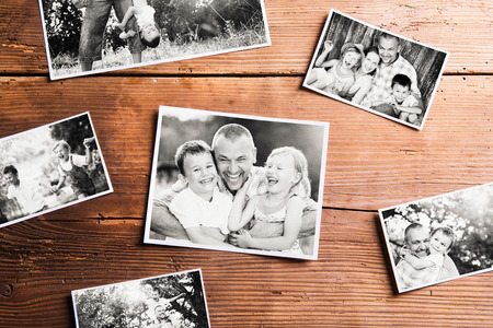 Fathers day composition. Various black-and-white family pictures. Studio shot on wooden background.