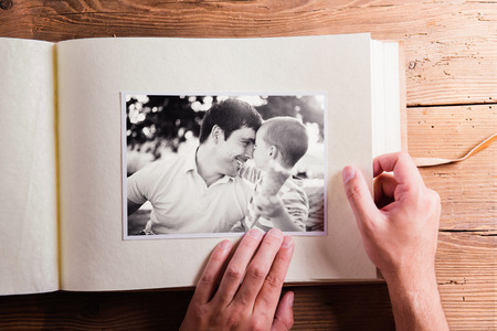 album: Fathers day composition. Hands of unrecognizable man holding a photo album, black-and-white pictures. Studio shot on wooden background.