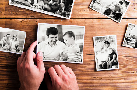 blackandwhite: Fathers day composition. Hands of unrecognizable man holding  black-and-white photo. Studio shot on wooden background.