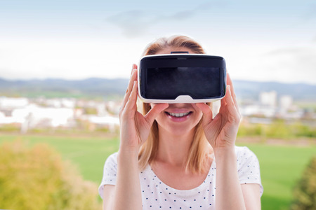 goggle: Blond woman wearing virtual reality goggles standing in a kitchen