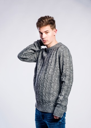 young boys: Teenage boy in jeans and gray sweater, young man, studio shot on gray background Stock Photo