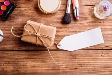 make a gift: Little package with empty tag and various make up products. Studio shot on wooden background. Copy space.