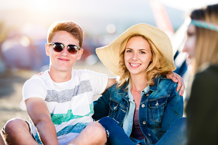 sitting on the ground: Teenage boy and girl at summer music festival, sitting on the ground, smiling, having fun Stock Photo