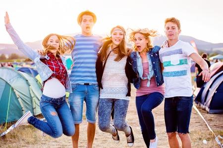 夏の音楽祭の十代の男の子と女の子のグループ ジャンプ、晴れた日