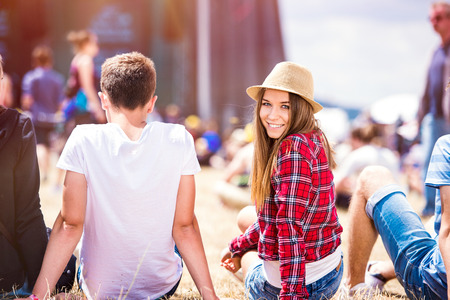 back ground: Teenage boy and girl at summer music festival, sitting on the grass in front of stage, rear view Stock Photo