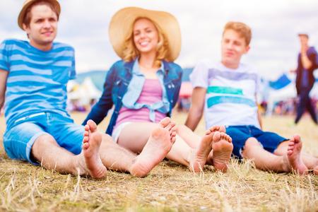 Gruppo di ragazzi adolescenti e ragazze al festival musicale estivo, seduto a terra