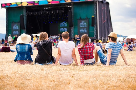 Group of teenagers at summer music festival, sitting on the grass in front of stage, rear view
