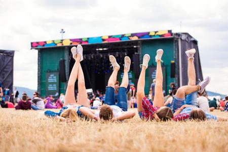 Nohy teenagerů na letní hudební festival, ležící na trávě v přední části jeviště, pohled zezadu