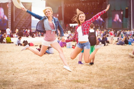 Adolescenti al festival estivo di musica, di fronte palco, saltando
