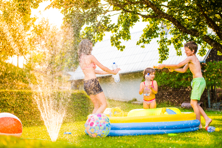 Unrecognizable boy splashing girls with water gun in garden swimming pool, sunny summer day, back yard