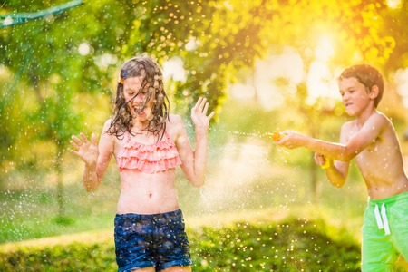 water gun: Boy splashing girl with water gun, fun in garden, sunny summer day, back yard