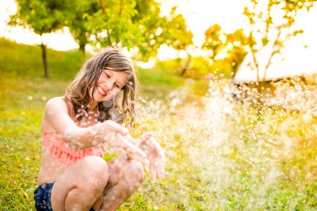 petite fille maillot de bain: Fille en bikini assis à l'arrosage, jardin verdoyant d'été ensoleillée
