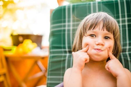 back yard: Cute little girl outside in garden holding her cheeks, sunny summer back yard Stock Photo