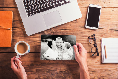 blackandwhite: Fathers day composition. Hands of unrecognizable man holding black-and-white photos. Office desk. Studio shot on wooden background.