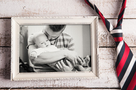 Fathers day composition. Black and white picture of father and daugter in picture frame, colorful tie. Wooden background. Studio shot on wooden background. Stock Photo
