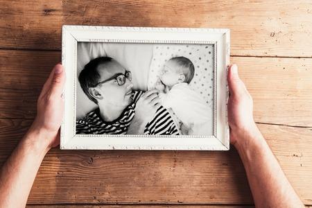 Composición del día de padres. Manos del hombre irreconocible que sostiene foto en blanco y negro en el marco de imagen. Estudio tirado en el fondo de madera. Foto de archivo - 56997649