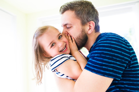 Primo piano di padre pantaloni a vita bassa che bacia la sua piccola figlia, giornata di sole Archivio Fotografico