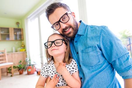 Padre con su pequeña hija en gafas negras inconformista, día soleado en el interior