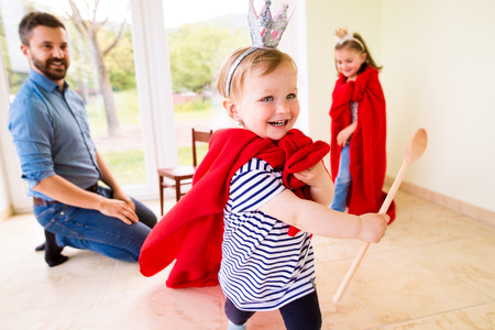 capes: Hipster father with his cute little princess daughters wearing red capes