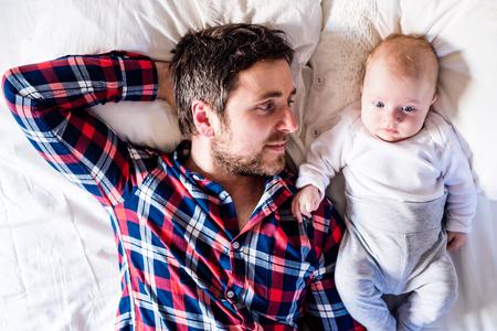 生まれたばかりのかわいい赤ちゃんの少年の父親の隣のベッドの上で横になっています。