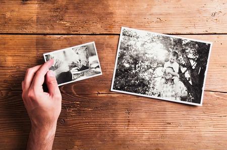 Vaders dag samenstelling. Handen van onherkenbare man met zwart-wit foto. Studio opname op houten achtergrond.