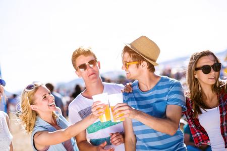 Groep van tiener jongens en meisjes met bieren in een menigte in de zomer muziekfestival, zonnige dag