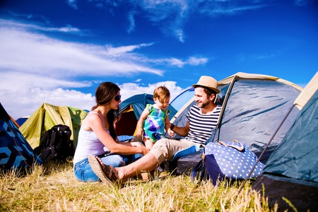 cool kids: Young couple with their baby daughter in a tent at summer music festival