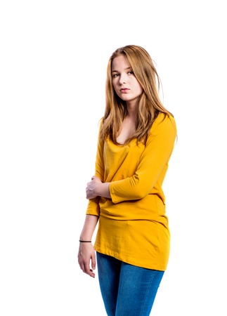 long sleeved: Teenage girl in jeans and long sleeved yellow t-shirt, young woman, studio shot on white background, isolated Stock Photo