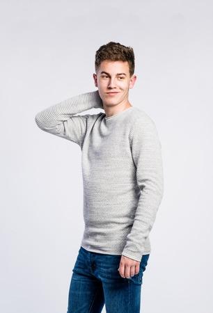 jeans apretados: adolescente en pantalones vaqueros y un suéter gris, joven, tiro del estudio sobre fondo gris