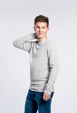 tight jeans: Teenage boy in jeans and gray sweater, young man, studio shot on gray background Stock Photo