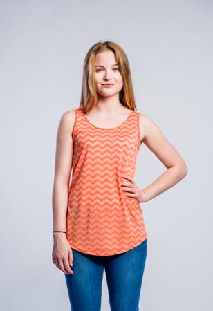 jeans apretados: Adolescente en pantalones vaqueros y camiseta de color naranja, mujer joven, tiro del estudio sobre fondo gris